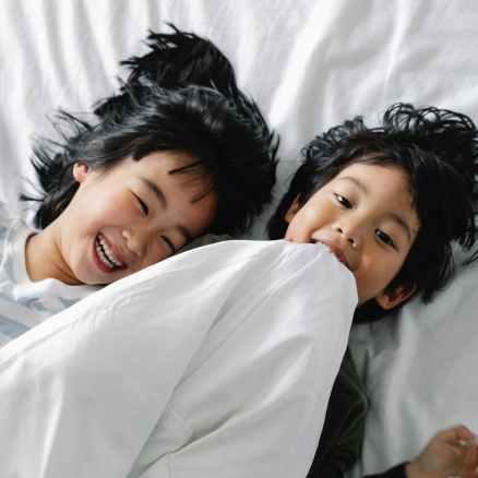 kids lying on white bed