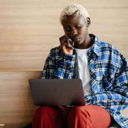 black woman talking on smartphone while surfing internet on laptop