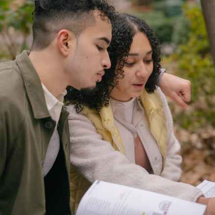 hispanic couple of students in park preparing for exams