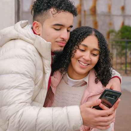 smiling young ethnic couple hugging and using smartphone on street