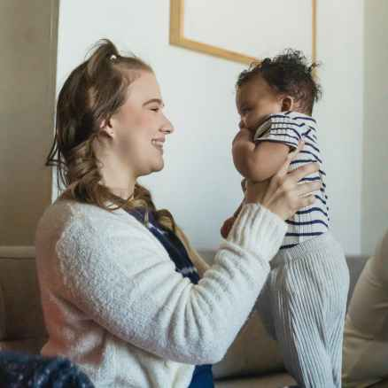 optimistic mother with black baby in hands