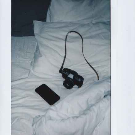 instant shot of camera and smartphone on white bed