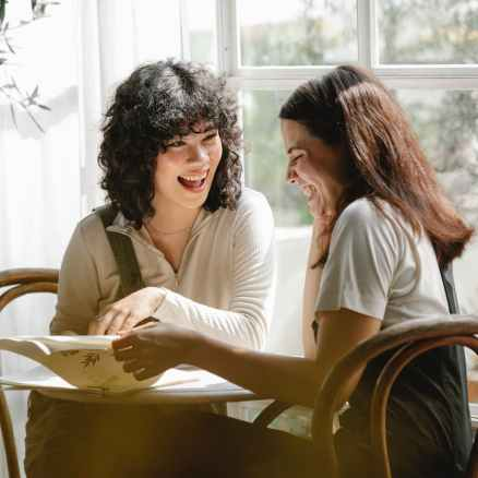 cheerful diverse girlfriends reading document at table