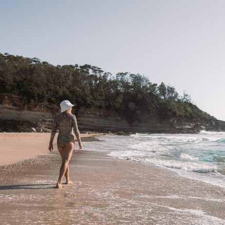 unrecognizable woman strolling along sandy beach