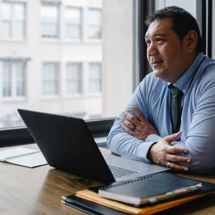 positive ethnic boss using laptop in light office