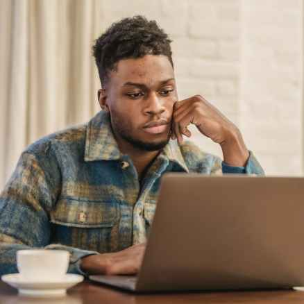 concentrated young black guy sitting at table and working remotely on netbook
