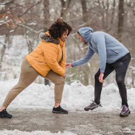 coach correcting black woman while doing lunges in park