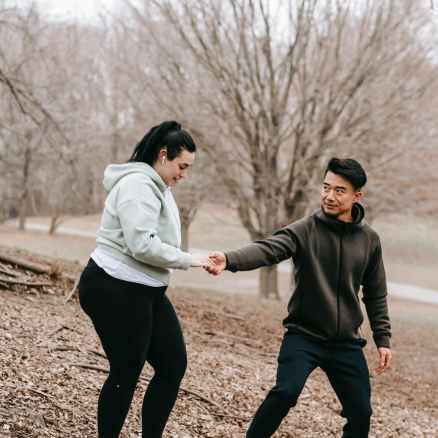 young energetic asian coach supporting plus size woman