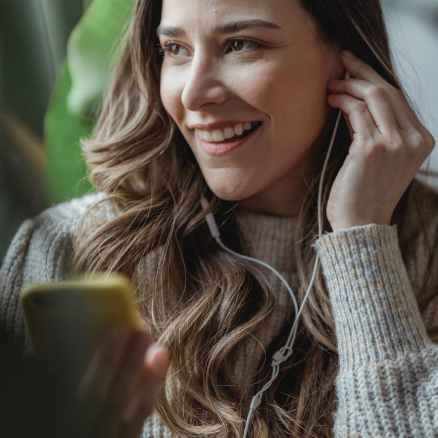 crop smiling woman listening to music in earphones